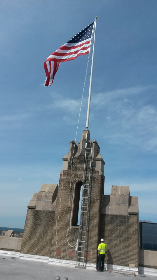 Flag on top of a parapet wall after being repainted by Mr. Flagpole Maintenance